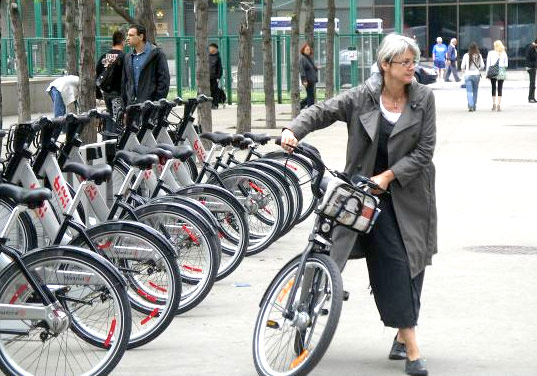 a woman using a public bike, velib, biki bike, public bike systems, paris bike share, bike sharing, public bike sharing, bike rental, greener cities, boston bike